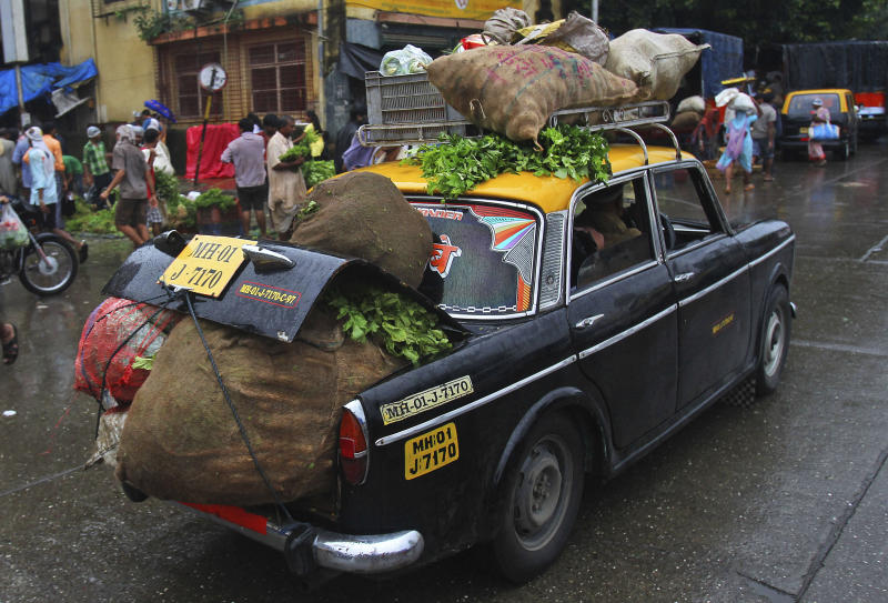A Premier Padmini taxi is overloaded with vegetables as it drives through a street in Mumbai, India, Friday, Aug 2, 2013. More than 4500 Premier Padmini taxis are expected to be banned from the roads in Mumbai this year, starting in August, in line with a government order that bans cabs that are more than 20 years old. (AP Photo/Rafiq Maqbool)