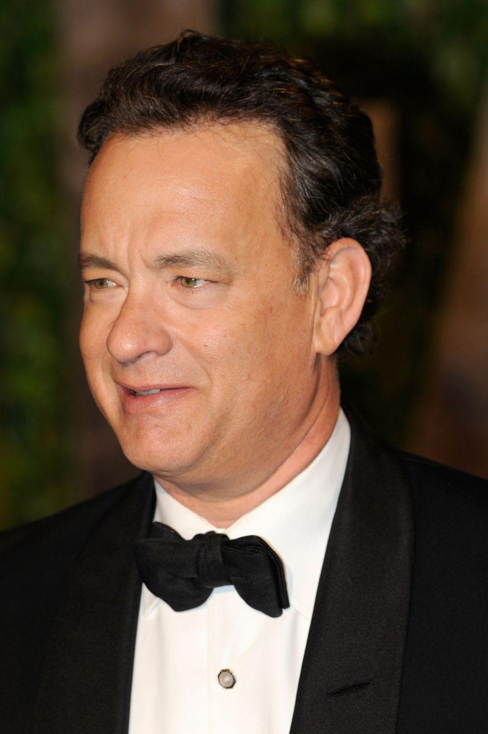 <p>Tom Hanks' natural brown curly hair is seen here as he arrives at the Vanity Fair Oscar Party in 2010. </p>