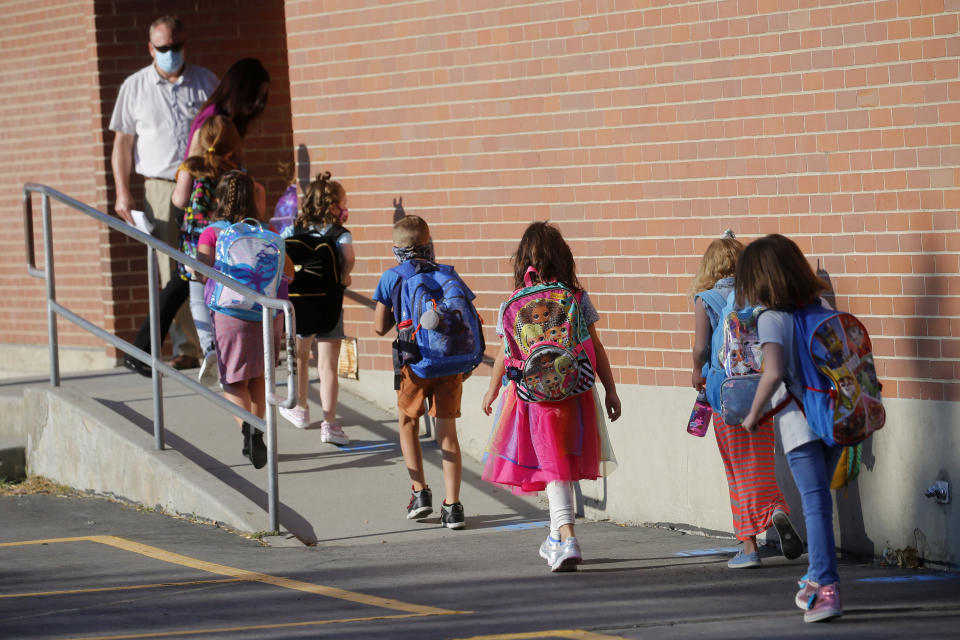 """FILE - In this Aug. 17, 2020, file photo, students walk into Liberty Elementary School during the first day of class in Murray, Utah. Virus cases are surging across Europe and many U.S. states, but responses by leaders are miles apart, with officials in Ireland, France and elsewhere imposing curfews and restricting gatherings even as some U.S. governors resist mask mandates or more aggressive measures. In Utah, a spike in cases since school reopened has created a dynamic that Republican Gov. Gary Herbert has called """"unsustainable."""" (AP Photo/Rick Bowmer, File)"""