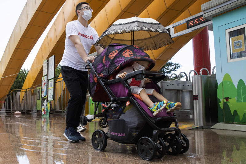 A man and a child wearing masks to curb the spread of the new coronavirus visit a local park in Beijing on Saturday, May 23, 2020. New coronavirus cases dropped to zero in China for the first time Saturday but overwhelmed hospitals across Latin America – both in countries lax about lockdowns and those lauded for firm, early confinement. (AP Photo/Ng Han Guan)