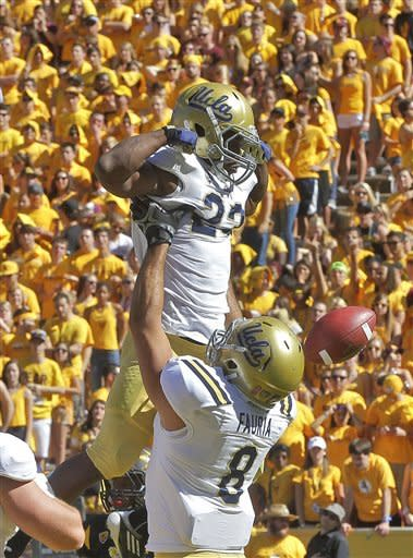 UCLA running back Johnathan Franklin (23) is hoisted by Joseph Fauria (8) after scoring a touchdown against Arizona State during the first half of an NCAA college football game, Saturday, Oct. 27, 2012, in Tempe, Ariz. (AP Photo/Matt York)