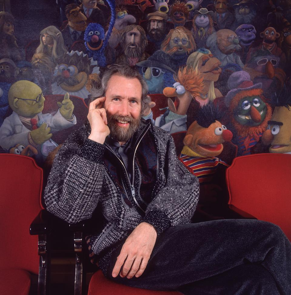 1986:  Portrait of American puppeteer Jim Henson (1936 - 1990) sitting in a theater chair in front of a painting of his creation, The Muppets.  (Photo by Nancy R. Schiff/Hulton Archive/Getty Images)