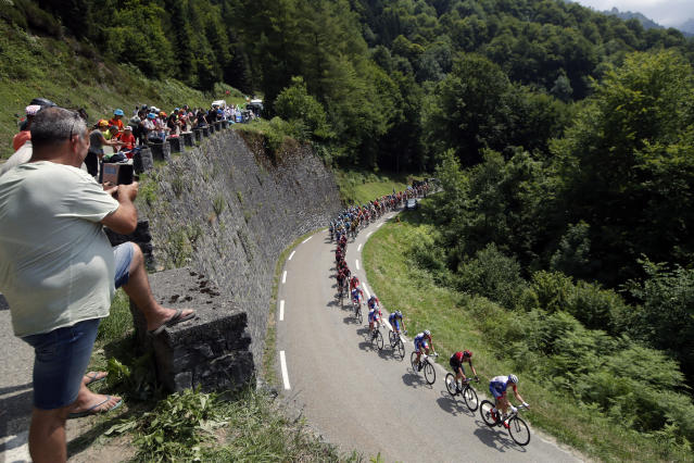 Spectators watch the pack as he rides during the fourteenth stage of the Tour de France cycling race over 117,5 kilometers (73 miles) with start in Tarbes and finish at the Tourmalet pass, France, Saturday, July 20, 2019. (AP Photo/ Christophe Ena)