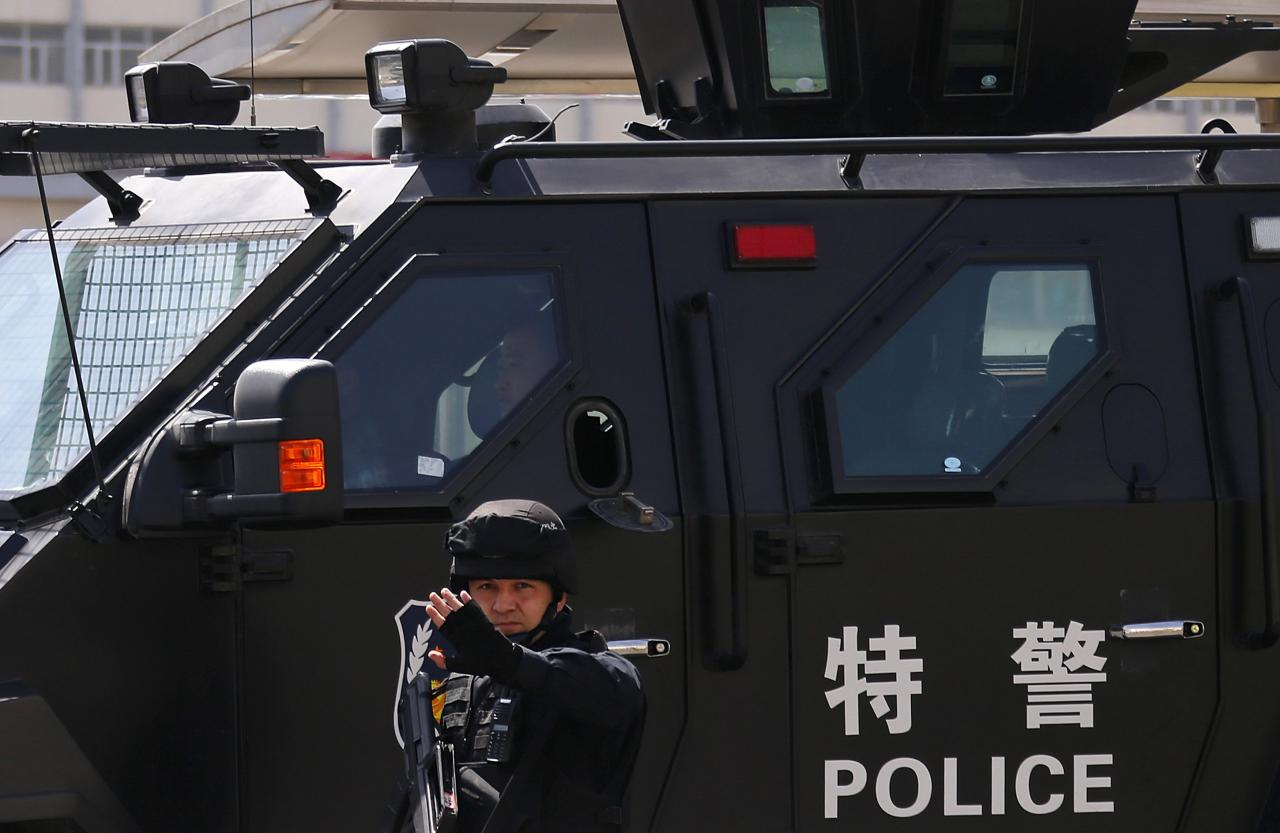 A police from Special Weapons and Tactics (SWAT) team gestures next to a police car outside the South Railway Station, where three people were killed and 79 wounded in a bomb and knife attack on Wednesday, in Urumqi, Xinjiang Uighur Autonomous region, May 1, 2014. A bombing in western China has raised concerns about the apparent sophistication and daring of the attack, possibly timed to coincide with a visit to the heavily Muslim region by President Xi Jinping. REUTERS/Petar Kujundzic (CHINA - Tags: CRIME LAW CIVIL UNREST)