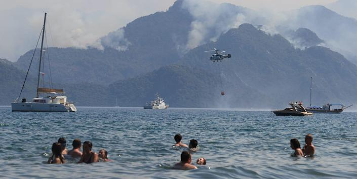 People in the water looking at a hill with smoke rising