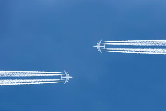 Two planes flying parallel, toward each other, with jet trails showing.
