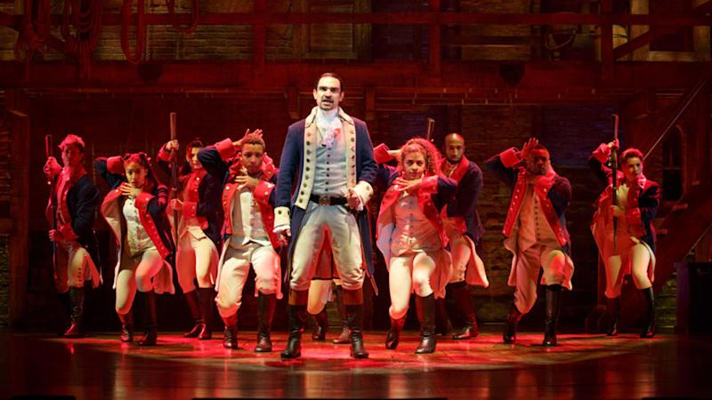 The cast of Hamilton onstage beneath red lighting.