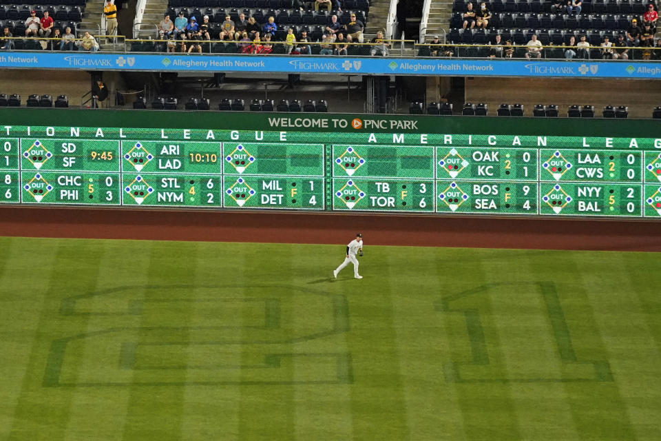 The No. 21 is cut into the right field grass at PNC Park in honor of Roberto Clemente Day, during a baseball game between the Pittsburgh Pirates and the Cincinnati Reds in Pittsburgh, Wednesday, Sept. 15, 2021. Playing right field for the Pirates is Yoshi Tsutsugo. (AP Photo/Gene J. Puskar)