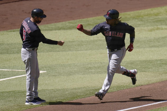 Cleveland Indians' Jose Ramirez, right, celebrates his home run against the Arizona Diamondbacks with third base coach Mike Sarbaugh during the first inning of a spring training baseball game at Chase Field Tuesday, March 30, 2021, in Phoenix. (AP Photo/Ross D. Franklin)