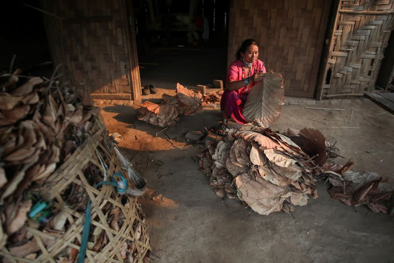 A woman prepares leaves for the roof of her house in the Kayan village where people, who fled from Myanmar during the 1990s war between Myanmar's army and ethnic army groups, live in Mae Hong Son