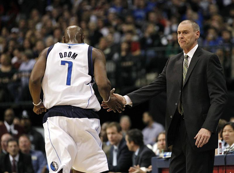 Dallas Mavericks head coach Rick Carlisle, right, reaches to Lamar Odom (7) as he comes out of the game and heads to the bench during the first half of an NBA basketball game against the Utah Jazz, Saturday, March 3, 2012, in Dallas. (AP Photo/LM Otero)