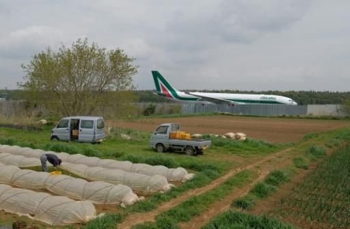 A farmer works on a plot beside Narita airport, Tokyo's main international gateway