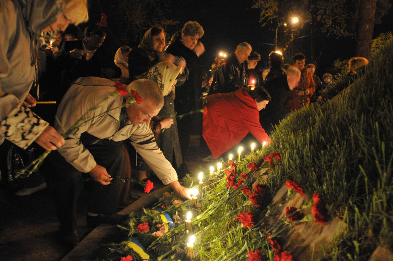 People lay flowers and light candles to honor the memory of the victims of the Chernobyl disaster in Kiev, Ukraine,Thursday, April 26, 2012. Ukraine marked the 26th anniversary since the Chernobyl power station exploded. (AP Photo/Sergei Chuzavkov)