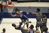 Kansas State guard Mike McGuirl (00) shoots while defended by West Virginia forwards Gabe Osabuohien (3) and Jalen Bridges (2) during the second half of an NCAA college basketball game Saturday, Feb. 27, 2021, in Morgantown, W.Va. (AP Photo/Kathleen Batten)