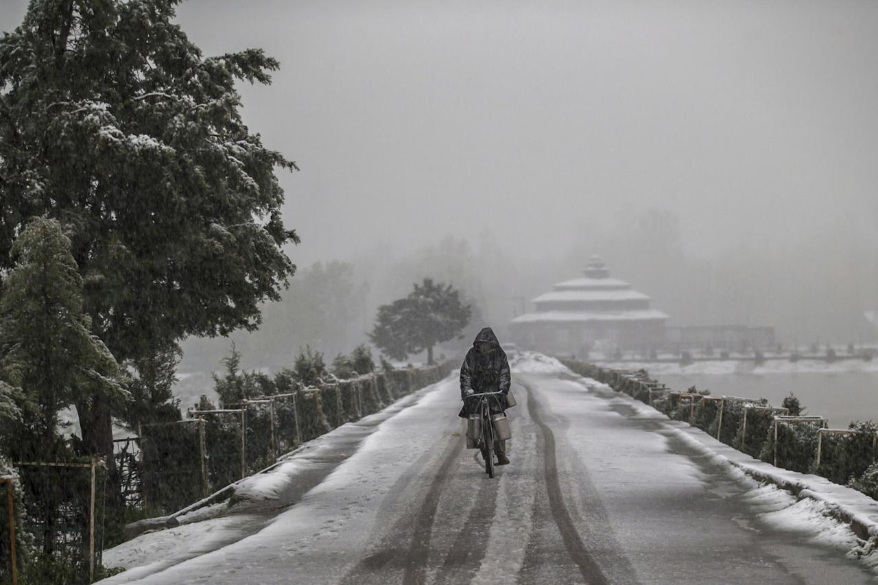 <p>A Kashmiri milkman cycles on a snow-covered road on the outskirts of Srinagar, Kashmir, Thursday, April 6, 2017. (AP Photo/Dar Yasin) </p>