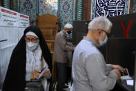 Voters fill out their ballot papers during the presidential elections at a polling station in Tehran, Iran, Friday, June 18, 2021. Iran began voting Friday in a presidential election tipped in the favor of a hard-line protege of Supreme Leader Ayatollah Ali Khamenei, fueling public apathy and sparking calls for a boycott in the Islamic Republic. (AP Photo/Vahid Salemi)