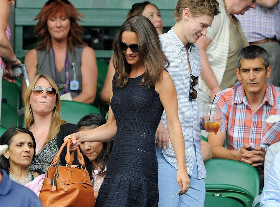 <p>Middleton wore a navy dress with tan bag. </p>