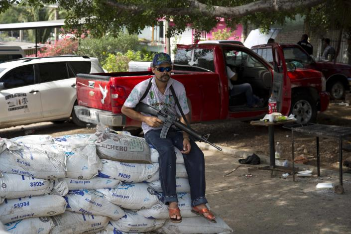 An armed man belonging to the Self-Defense Council of Michoacan (CAM) sits on sandbags at a checkpoint set up by the self-defense group in La Mira on the outskirts of the seaport of Lazaro Cardenas in western Mexico, Friday, May 9, 2014. Mexico's government plans on Saturday to begin demobilizing the vigilante movement that largely expelled the Knights Templar cartel when state and local authorities couldn't. But tension remained on Friday in the coastal part of the state outside the port of Lazaro Cardenas, where some self-defense groups plan to continue as they are, defending their territory without registering their arms. (AP Photo/Eduardo Verdugo)