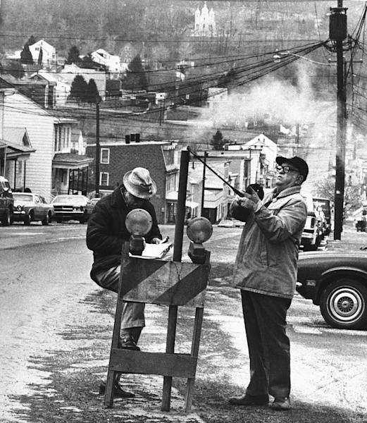 FILE - In this April, 1981, file photo, U.S. Bureau of Mines' John Stockalis, right, and Dan Lewis drop a thermometer through a hole on Main Street in Centralia, Pa., to measure the heat from a shaft mine blaze that was burning under the town. The attorney for the few remaining residents of the central Pennsylvania coal town that was decimated by a 50-year-old mine fire said on Thursday, Oct. 31, 2013, that they have settled their lawsuit against state officials who have been trying for years to evict them. The settlement allows eight Centralia residents to stay in their homes for as long as they live and it also includes a cash payout. (AP Photo/Paul Vathis, File)