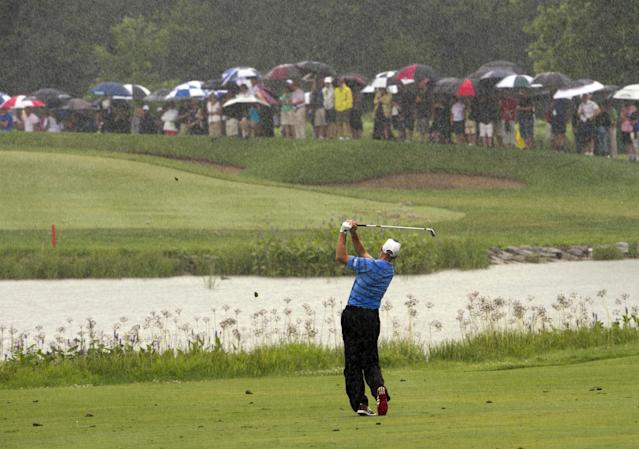 Jim Furyk hits from the fairway on the 15th hole as the rain comes down during final round play at the Canadian Open golf championship Sunday, July 27, 2014, at Royal Montreal golf club in Montreal. (AP Photo/The Canadian Press, Ryan Remiorz)