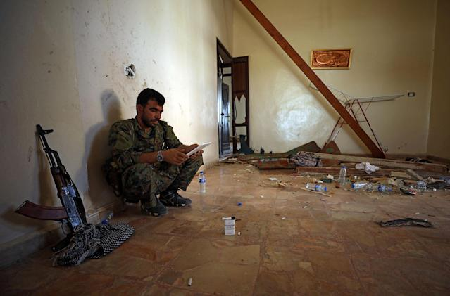 <p>A Syrian Democratic Forces (SDF) fighter uses a tablet as he sits inside a room in the al-Mishlab district at Raqqa's southeastern outskirts, Syria June 7, 2017. Picture taken June 7, 2017. (Photo: Rodi Said/Reuters) </p>