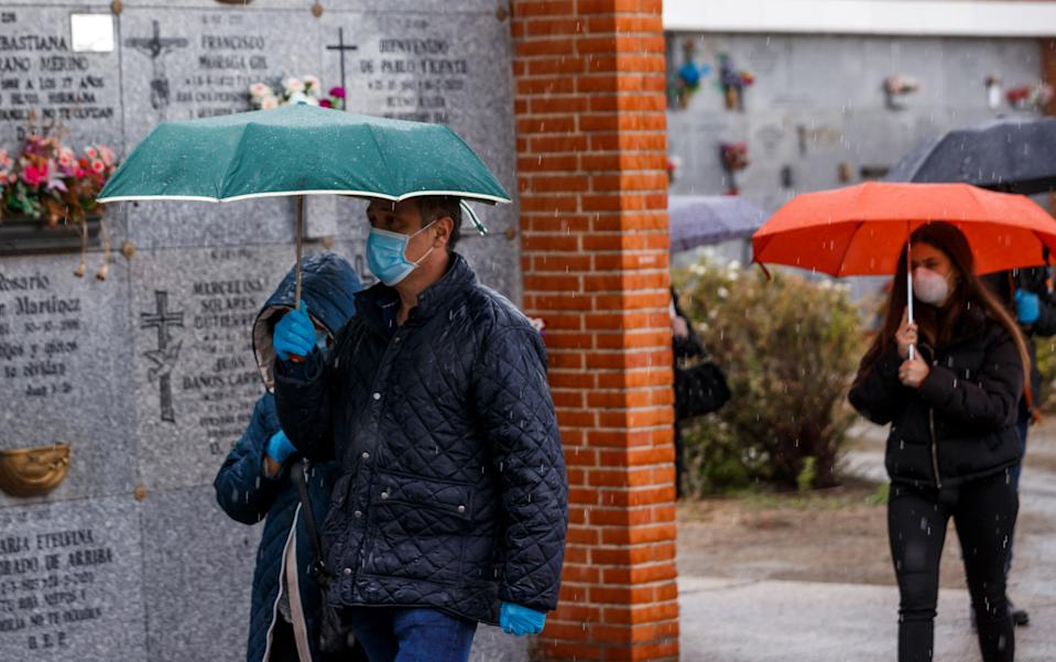 People wearing face masks arrive at the South Municipal cemetery in Madrid, on March 23, 2020, to attend the burial of a man who died of the new coronavirus. - The coronavirus death toll in Spain surged to 2,182 after 462 people died within 24 hours, the health ministry said. The death rate showed a 27-percent increase on the figures released a day earlier, with the number of confirmed cases of COVID-19 rising to 33,089 in Spain, one of the worst-hit countries in the world after China and Italy. (Photo by BALDESCA SAMPER / AFP) (Photo by BALDESCA SAMPER/AFP via Getty Images)