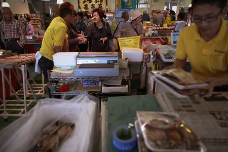 People buy fish at a market in the Iwaki town, south of the tsunami-crippled Daiichi nuclear power plant in Fukushima prefecture in this September 19, 2013 file photo. REUTERS/Damir Sagolj