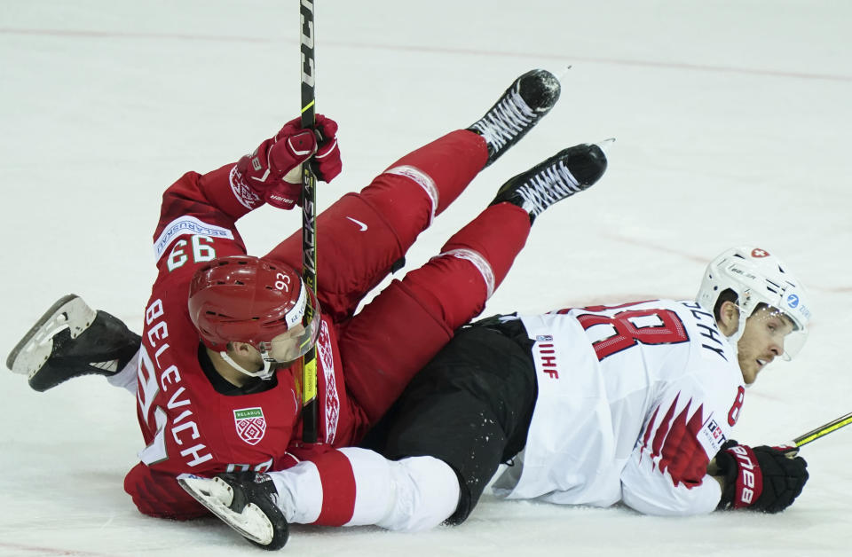 Andrei Belevich of Belarus, left, and Christoph Bertschy of Switzerland fight for a puck during the Ice Hockey World Championship group A match between the Belarus and Switzerland at the Olympic Sports Center in Riga, Latvia, Sunday May 30, 2021. (AP Photo/Roman Koksarov)