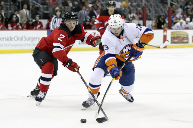 New Jersey Devils defenseman Colton White (2) fights for the puck against New York Islanders center Mathew Barzal (13) during the first period of a preseason NHL hockey game, Saturday, Sept. 21, 2019, in Newark, N.J. (AP Photo/Mary Altaffer)