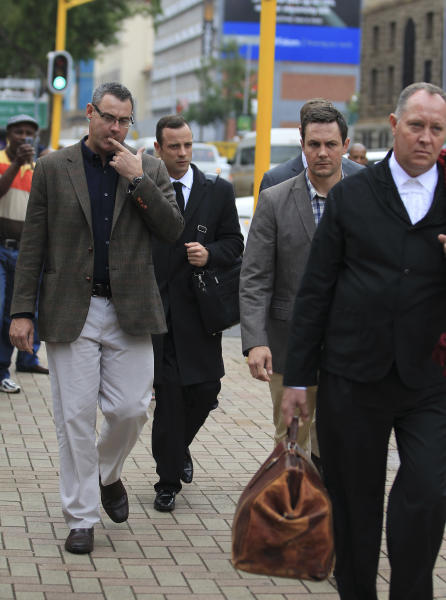 Oscar Pistorius, second from left, arrives at the high court in Pretoria, South Africa, Monday, March 10, 2014. The testimony in the first week of Pistorius' murder trial was jaw dropping at times, and more riveting evidence is expected as the prosecution seeks to prove beyond reasonable doubt that the double-amputee athlete intentionally shot dead his girlfriend Reeva Steenkamp, on Valentines Day in 2013. (AP Photo/Themba Hadebe)