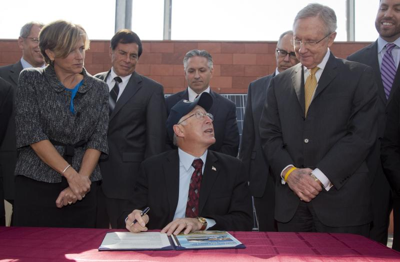 Flanked by Senate Majority Leader Harry Reid, D-Nev., right, and Bureau of Land Management state director Amy Leuders, left, Interior Secretary Ken Salazar prepares to sign a plan that sets aside 285,000 acres of public land for the development of large-scale solar power plants Friday, Oct. 12, 2012, in Las Vegas. The plan replaces the department's previous first-come, first-served system of approving solar projects, which let developers choose where they wanted to build utility-scale solar sites and allowed for land speculation. (AP Photo/Julie Jacobson)