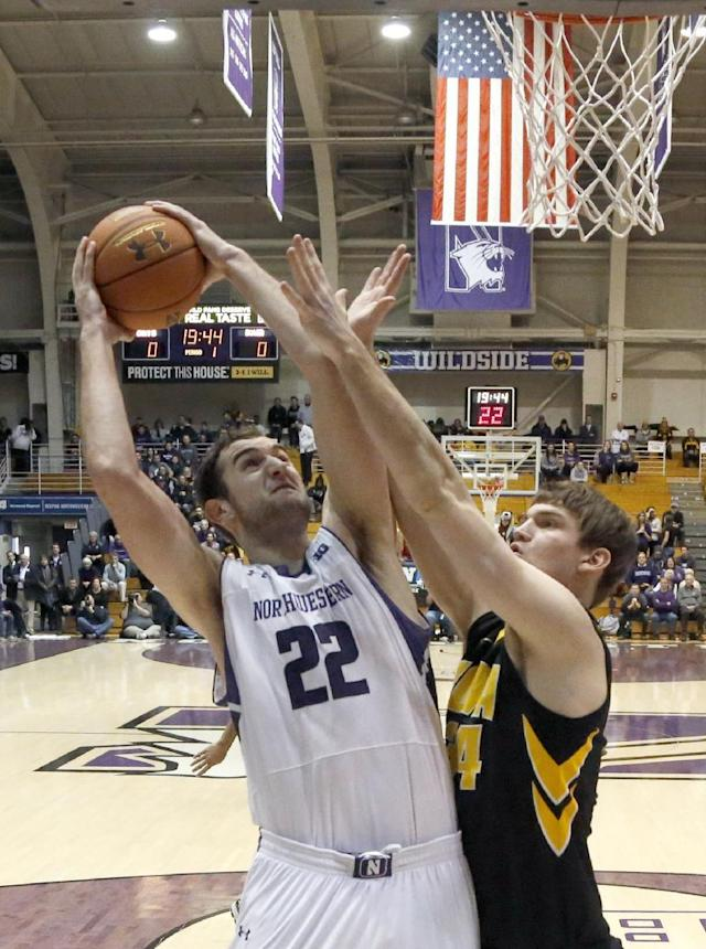 Northwestern center Alex Olah (22) shoots over Iowa center Adam Woodbury during the first half of an NCAA college basketball game Saturday, Jan. 25, 2014, in Evanston, Ill. (AP Photo/Charles Rex Arbogast)