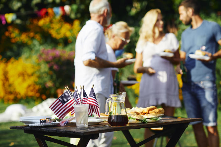 Multi-generation family on picnic in back yard celebrating 4th of July - Independence Day. Selective focus on food and drink with american flags on the table.