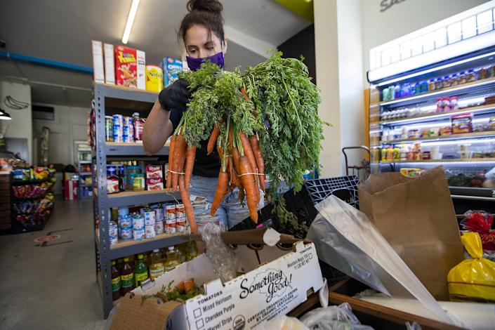"Luz Arango bags food donated by Atwater Village Farmers Market to be distributed to neighborhood members in need. <span class=""copyright"">(Allen J. Schaben/Los Angeles Times)</span>"
