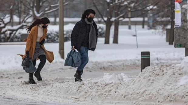 People wearing masks make their way through the snow in downtown Ottawa on Feb. 16, 2021.