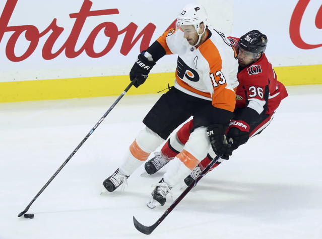 Philadelphia Flyers center Kevin Hayes (13) grabs the puck as Ottawa Senators center Colin White (36) pressures during the first period of an NHL hockey game, Saturday, Dec. 21, 2019, in Ottawa, Ontario. (Fred Chartrand/The Canadian Press via AP)