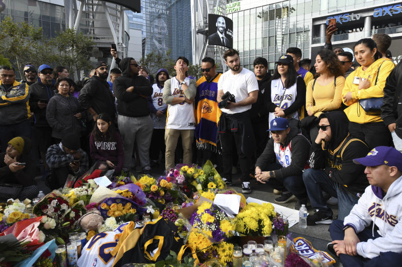 People gather at a memorial for Kobe Bryant near Staples Center Sunday, Jan. 26, 2020, in Los Angeles. Bryant, the 18-time NBA All-Star who won five championships and became one of the greatest basketball players of his generation during a 20-year career with the Los Angeles Lakers, died in a helicopter crash Sunday. (AP Photo/Michael Owen Baker)