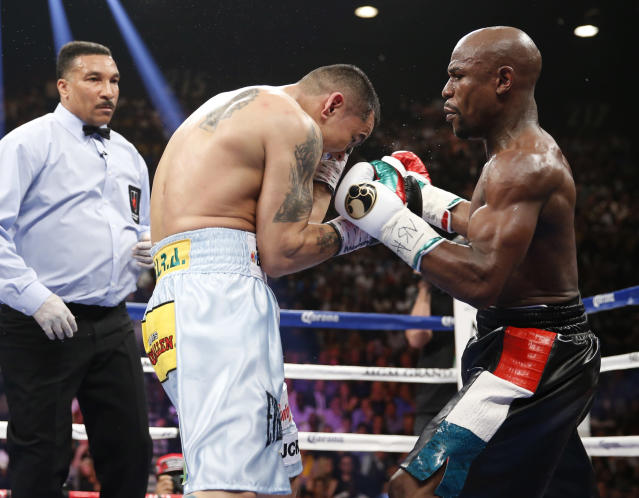 Floyd Mayweather Jr., right, trades blows with Marcos Maidana, from Argentina, in their WBC-WBA welterweight title boxing fight Saturday, May 3, 2014, in Las Vegas. Referee Tony Weeks is at left. (AP Photo/Eric Jamison)