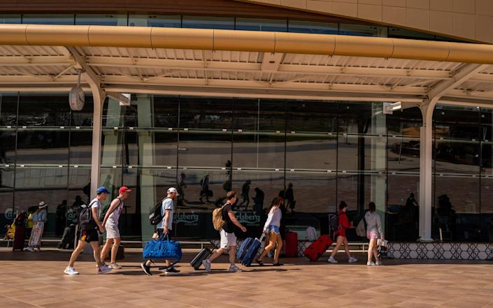 Tourists wheel luggage from the arrivals terminal at Faro Airport in Faro, Portugal - Jose Sarmento Matos/Bloomberg