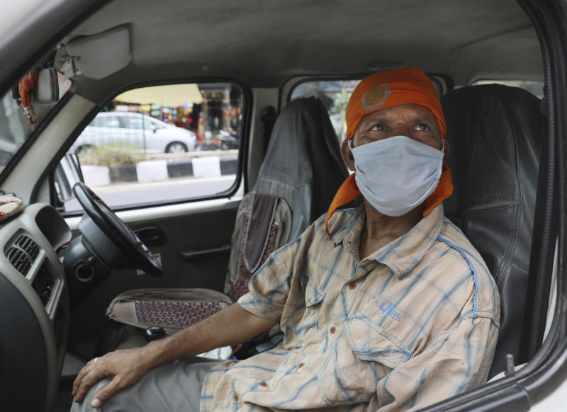 Indian driver Gangaram, 48, who lost his job and business because of the new coronavirus lockdown, sits in his vehicle in New Delhi, India Thursday, June 4, 2020. Gangaram used to pick and drop schoolchildren from a New Delhi neighborhood. The job assured him of slim financial security. to relaunch the economy. That's the harsh truth facing workers laid off around the world, from software companies in Israel to restaurants in Thailand and car factories in France, whose livelihoods fell victim to a virus-driven recession that's accelerating decline in struggling industries and upheaval across the global workforce. (AP Photo/Manish Swarup)