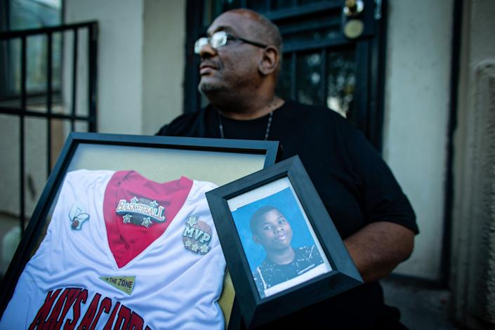 "Donald Williams sits on the stoop of his home holding a photo and basketball jersey of his late son, Deon Williams, a 13-year-old who was shot and killed. <span class=""copyright"">(Jason Armond / Los Angeles Times)</span>"