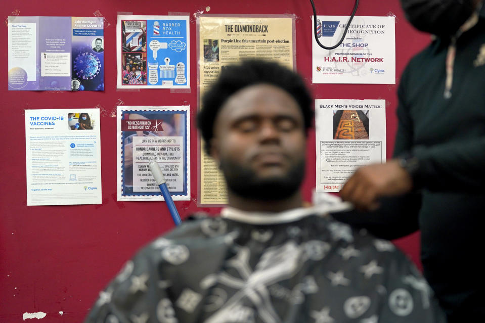 Health literature and a certificate are displayed on the wall as a patron gets a hair cut, Friday, April 9, 2021, in Hyattsville, Md. Barbers at The Shop are members of the Health Advocates In Reach & Research (HAIR) program, which helps barbers and hair stylists to get certified to talk to community members about health. During the COVID-19 pandemic, a team of certified barbers have been providing factual information to customers about vaccines, a topic that historically has not been trusted by members of black communities because of the health abuse the race has endured over the years. (AP Photo/Julio Cortez)