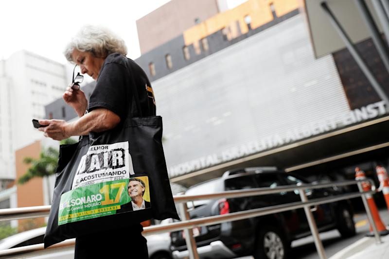 A woman looks at her mobile as she wears a sticker on her bag with the image of presidential candidate Jair Bolsonaro in front of the Albert Einstein hospital, where Bolsonaro is hospitalized, in Sao Paulo, Brazil September 28, 2018. REUTERS/Nacho Doce