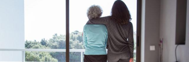 a young woman looking at the window with her arm around an older woman