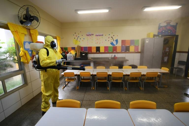 A federal district employee disinfects a public school as a measure against the spread of the new coronavirus in Brasilia, Brazil's capital. The local government has begun preparations for the safe reopening of schools in early September