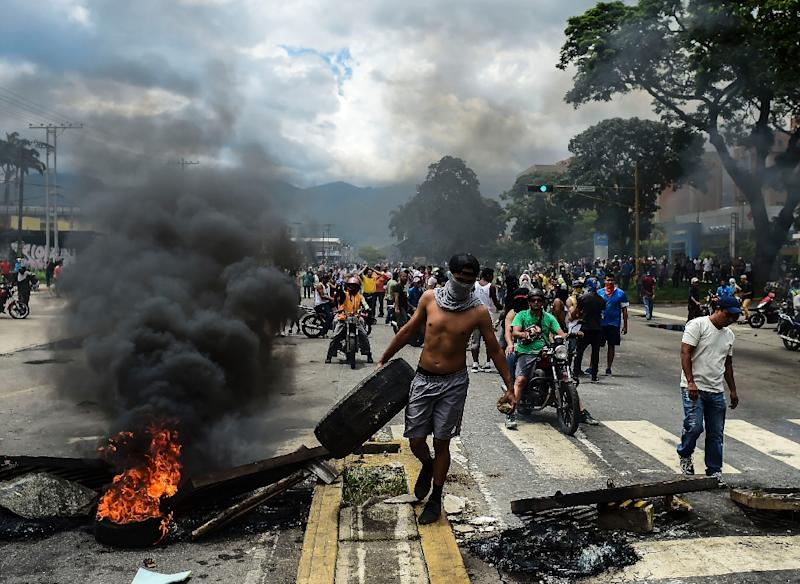 Venezuelan opposition activists build a barricade during clashes in Valencia, on August 6, 2017