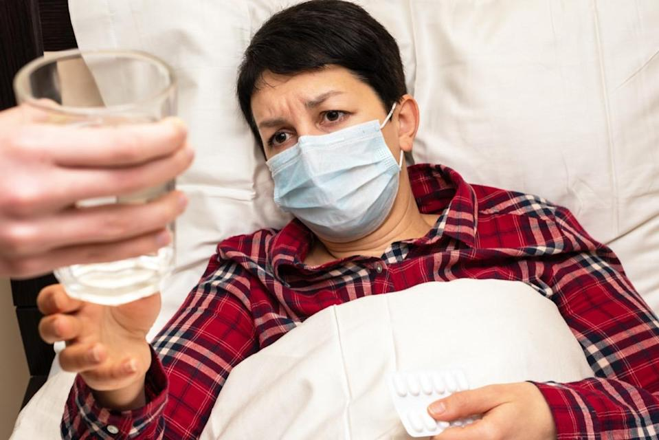 Sick woman in medical mask lying on the bed is given glass of water to take pills. Family care for the sick concept