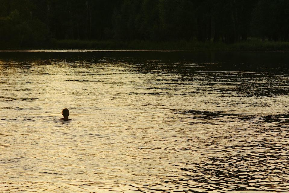 Silhouette of a boy in river