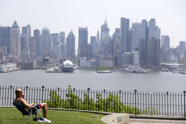 A man enjoys the sunshine and the New York City skyline from a park in Weehawken, N.J. (AP Photo/Seth Wenig)