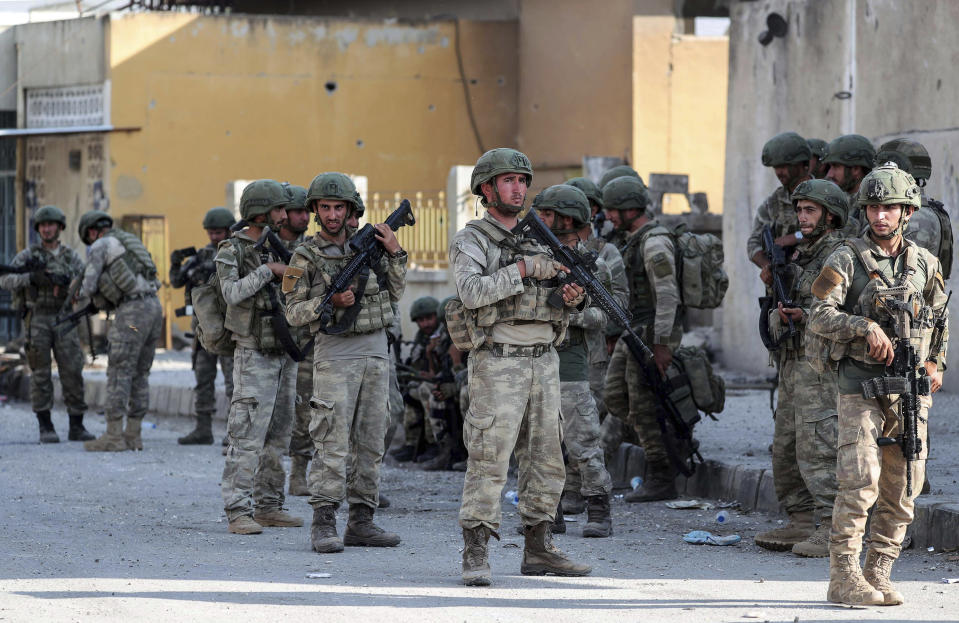 Turkish soldiers secure in Syrian town of Ras al Ayn, northeastern Syria, Wednesday, Oct. 23, 2019. Turkish media reports say Turkish troops and their allied Syrian opposition forces are securing a town in northeast Syria after Syrian Kurdish fighters pulled out of the area.(Ugur Can/DHA via AP)
